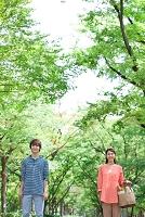 春の並木道に立つカップル