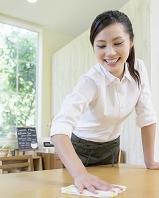 テーブルを拭く日本人女性店員