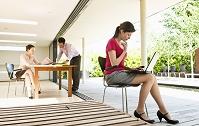テラスがあるオフィスで働く外国人ビジネス女性