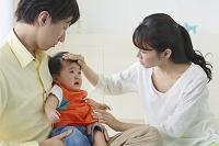 泣く赤ちゃんを抱っこするお父さんとお母さん