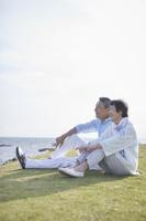 芝生の上でくつろぐ日本人シニア夫婦