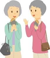 食べ歩きを楽しむ日本人のシニア女性二人