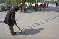 路上に漢字を書く女性 北海公園