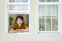 窓から顔を出す笑顔のシニア日本人女性