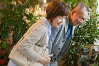 花屋で観葉植物を見るシニア夫婦