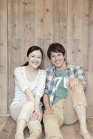 木の床に座って微笑む若いカップル