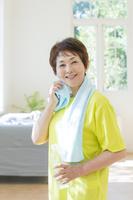 タオルで顔を拭く笑顔のシニア日本人女性