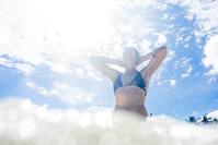 海で日差しを浴びる女性