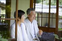 縁側でお茶を飲む日本人シニア夫婦