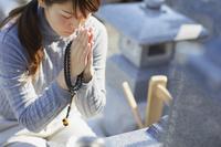 お墓参りをする日本人女性
