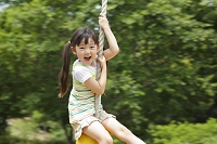 公園の遊具で遊ぶ元気な日本人の女の子