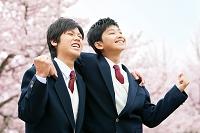 桜とガッツポーズの男子高校生