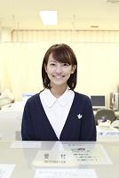 病院の受付で微笑む日本人女性職員