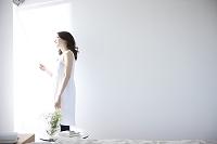 寝室のロールカーテンを開ける日本人女性