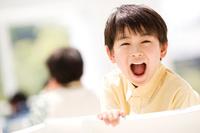 振り向いて大きな口を開ける日本人の男の子