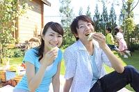 サンドイッチを食べながらピクニックを楽しむ夫婦