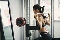 ラットプルマシンでトレーニングをする日本人女性