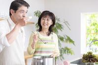 料理して味見する中高年夫婦