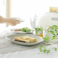 バターをのせたトーストと朝食の準備をする女性の手元