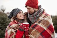 毛布にくるまる若いカップル