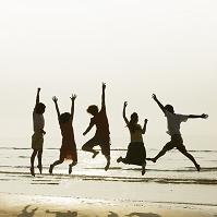 海辺でジャンプする若者達