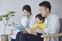 息子に絵本の読み聞かせをする両親