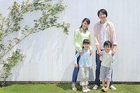 白い壁の前に並ぶ日本人家族