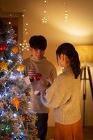 クリスマスツリーに飾り付けをするカップル