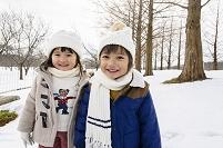 雪の積もる歩道で立ち止まる子供達