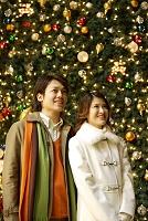 クリスマスツリーの前で寄り添うカップル