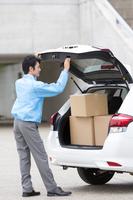 営業車に荷物を積むビジネス男性