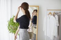 鏡で身なりをチェックする女性