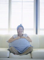 クッションを抱えソファに座る日本人女性
