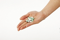カプセルの薬をのせた手の平
