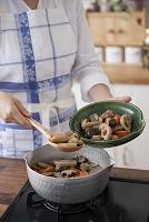筑前煮を鍋から皿へ盛り付ける女性