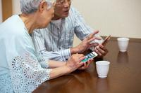 スマートフォンを操作する日本人シニア夫婦