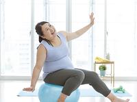 バランスボールで運動をする太った女性