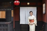 のれんの前に立つ着物の日本人女性
