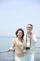 フェリーのデッキで海を見る中年夫婦