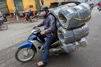 ベトナム バイクでホースを運ぶ人