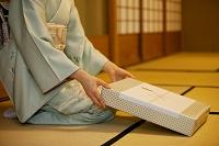 贈答品を差し出す着物の日本人女性