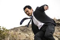 崖を降りる日本人ビジネスマン