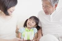 ソファに座る祖父母とプレゼントボックスを持つ孫