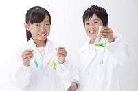 試験管とフラスコを持った白衣の日本人の子供