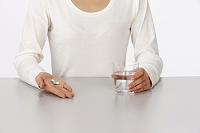 薬とコップの水を持つ女性の手