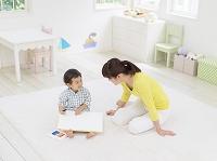 お絵描きをする男の子と座る母親