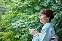 お茶を飲む着物を着た日本人女性