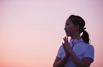 朝焼けの空と手を合わせる日本人女性
