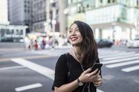 音楽を聴くスマートフォンを見る女性