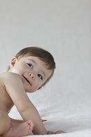 ベッドの上にお座りする外国人の赤ちゃん